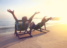 Happy couple sitting at sun chairs on the beach of Koh Samet at Stock Photos