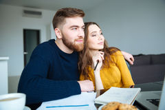 Happy couple sitting at the table with bills Stock Images