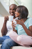 Happy couple sitting on their couch having coffee Stock Images