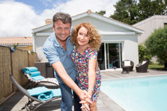Happy couple sitting in from of their new home with swimming pool Royalty Free Stock Photography