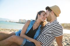 Happy couple sitting together on beach enjoying each other. Portrait of happy couple sitting together on beach enjoying each other Stock Photo