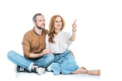 happy couple sitting together and pointing away with finger Stock Photos
