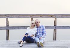 Happy couple sitting together on the river jetty. Fog. Sunset Royalty Free Stock Photo