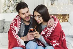 Couple relaxing with glass of warm wine on winter evening. Happy couple sitting together, sharing glass of mulled wine, copy space stock photo