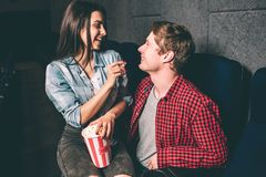 Happy couple is sitting together and smiling to each other. Girl is holding a piece of popcorn in one hand and a small. Basket of popcorn in the other hand Stock Image