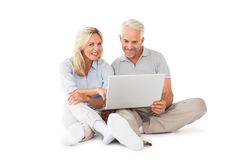 Happy couple sitting and using laptop Stock Photo