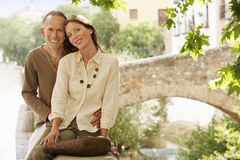 Happy Couple Sitting On Wall By Bridge Stock Photo
