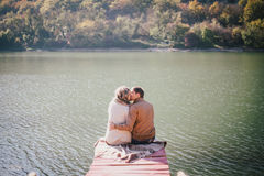 Happy couple sitting on a wooden bridge near lake Royalty Free Stock Image
