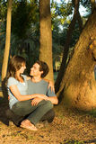 Happy Couple Sitting in the Woods. Vertical Stock Photography