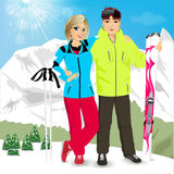 Happy couple skiers standing on edge of mountain peaks. Portrait of happy couple skiers standing on edge of mountain peaks on background of snowy mountains in Royalty Free Stock Photography