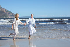 Happy couple skipping barefoot on the beach Royalty Free Stock Photos