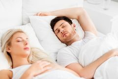 Happy couple sleeping in bed at home. People, rest and relationships concept - happy couple sleeping in bed at home stock photo