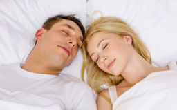 Happy couple sleeping in bed Stock Images