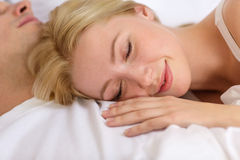Happy couple sleeping in bed Stock Image