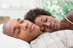 Happy couple sleeping in bed together Stock Images