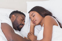 Happy couple sleeping in bed together Stock Photography