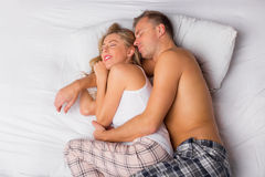 Happy couple sleeping and cuddling. In bed royalty free stock images