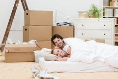 Happy couple sleeping on the floor in a new home Royalty Free Stock Image