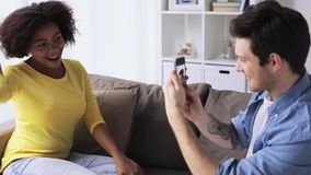 Happy couple with smartphone photographing at home stock video