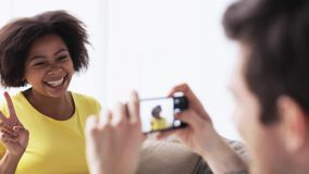 Happy couple with smartphone photographing at home stock footage