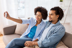 Happy couple with smartphone taking selfie at home Stock Image