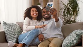 Happy couple with smartphone taking selfie at home stock video