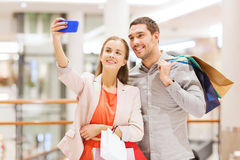 Happy couple with smartphone taking selfie in mall. Sale, consumerism, technology and people concept - happy young couple with shopping bags and smartphone Stock Images