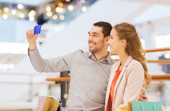 Happy couple with smartphone taking selfie in mall Stock Images