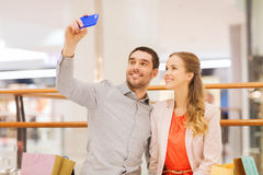 Happy couple with smartphone taking selfie in mall Stock Photos