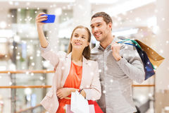 Happy couple with smartphone taking selfie in mall. Sale, consumerism, technology and people concept - happy young couple with shopping bags and smartphone Royalty Free Stock Photo
