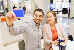 Happy couple with smartphone taking selfie in mall Royalty Free Stock Images