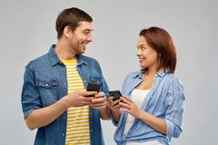 Happy couple with smartphones talking. Technology and people concept - happy couple with smartphones talking over grey background royalty free stock photography