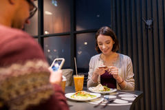 Happy couple with smartphones at vegan restaurant Stock Images