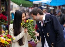 Happy couple smelling flowers together Royalty Free Stock Image