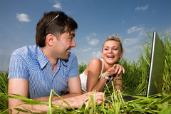 Happy couple are smile and laughing on laptop. Casual happy couple are talking  and laughing on a laptop computer outdoors. Lay on the green grass Royalty Free Stock Image