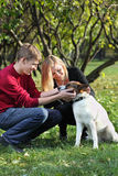 Happy couple smile and touch dog in park Stock Images