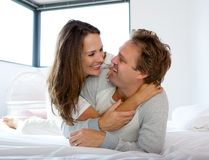 Happy couple smiling in bed Royalty Free Stock Photography