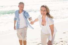 Happy couple smiling at camera. At the beach Royalty Free Stock Photos