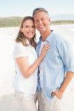 Happy couple smiling at camera. At the beach Royalty Free Stock Photo