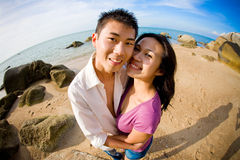Happy couple smiling at camera by the beach Royalty Free Stock Image