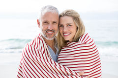 Happy couple smiling at camera with blanket around them Stock Image