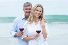 Happy couple smiling at camera and holding a glass of red wine Royalty Free Stock Images