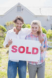 Happy couple smiling at camera holding sold sign Stock Photography