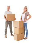 Happy couple smiling at camera with moving boxes Stock Photography
