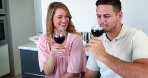 Happy couple smiling at the camera toasting with red wine. At home in the kitchen stock footage