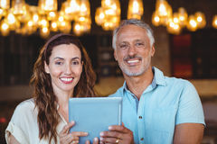 Happy couple smiling at camera and using tablet Stock Photos