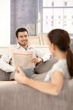 Happy couple smiling at each other sitting on sofa Stock Photos