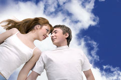 Happy couple smiling  having fun. Lying on clouds Royalty Free Stock Images
