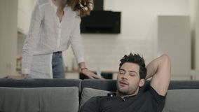 Happy couple smiling in living room. Concentrated man checking tv channels. stock video footage