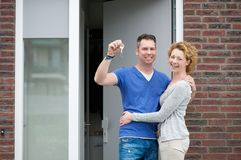Happy couple smiling outside new home Stock Photo
